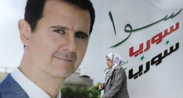 A Syrian woman walks past a placard bearing a portrait of President Bashar al-Assad in the city of Damascus on March 4, 2015. AFP PHOTO / LOUAI BESHARA