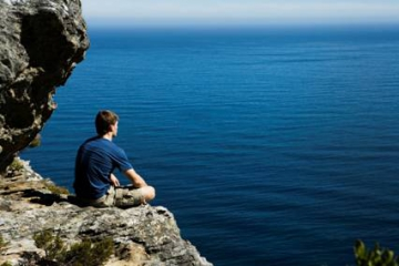 @Glowimages: Man Sitting on a Cliff